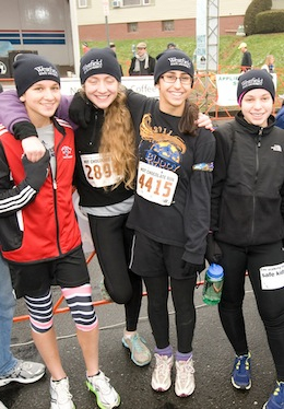 A group of girls wearing Westfield State University hats at a running race
